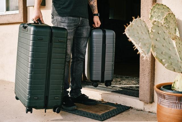homme portant deux valises